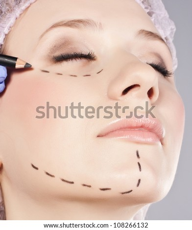 Drawn lines on woman's face, marks for facial plastic surgery - stock photo