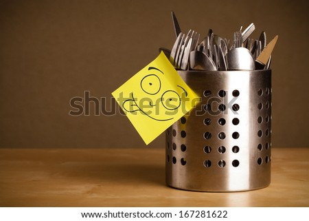 Drawn smiley face on a  note stuck on a cutlery case - stock photo