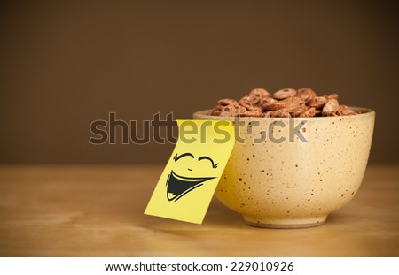 Drawn smiley face on a post-it note sticked on a cereal bowl - stock photo
