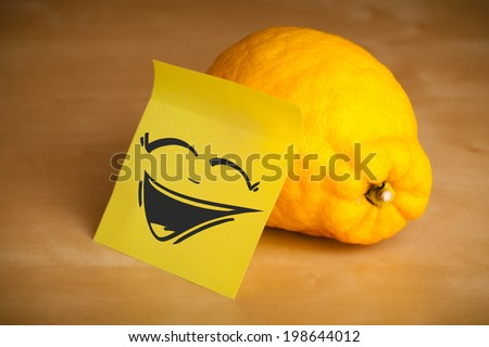Drawn smiley face on a post-it note sticked on a lemon