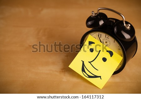 Drawn smiley face on a post-it note sticked on an alarm clock - stock photo