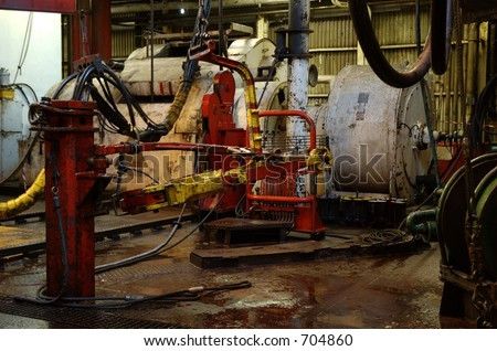 Drawworks, tongs and drill floor on an offshore oil rig - stock photo