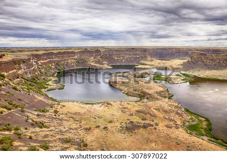 Dray Falls Park in Eastern Washington shows the edge of a dry waterfall over steep cliffs into a deep valley with a lake. - stock photo