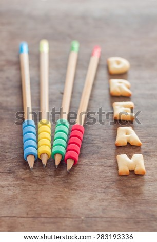 Dream alphabet biscuit on wooden table, stock photo - stock photo