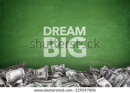 Dream big on blackboard with pile of dollar bills - stock photo