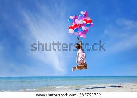 dream concept, girl flying on multicolored balloons in blue sky, imagination and creativity - stock photo