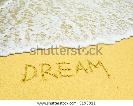 dream word written in the sandy beach - stock photo