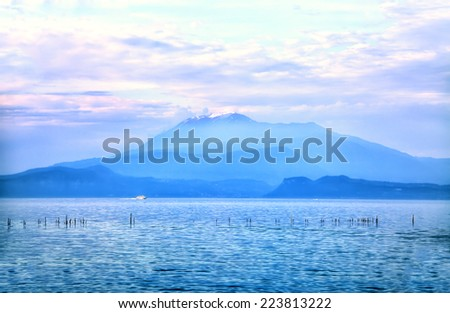 Dreamful view to a cloud-covered mountain by Sirmione at the Lake Garda - stock photo