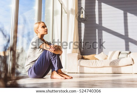 Dreamful young woman relaxing at home