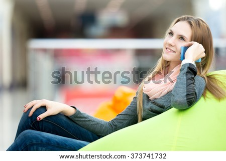 Dreamily smiling young woman in casual style clothes sitting on bean bag in office or shopping center, leisure area, using mobile phone, waiting for someone, copyspace - stock photo