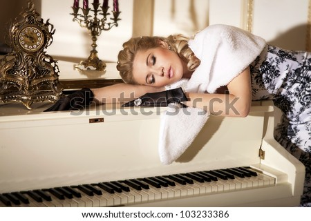 dreaming alluring woman pianist with grand piano in luxury hotel. Stylish rich slim girl in gloves elegant dress and fur with healthy glossy hair at villa apartment. Lady musician with diamond jewelry - stock photo