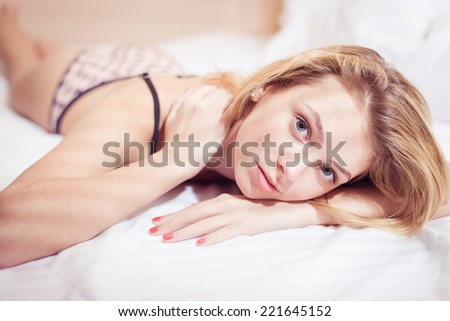 dreaming alone in bed: one elegant young lady sensual pinup blonde girl in lingerie having fun relaxing laying & tempting looking at camera on light bedroom copy space background portrait picture - stock photo