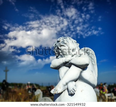 Dreaming Angel on the ball at cemetery against blue sky - stock photo
