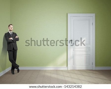 dreaming businessman standing in green room - stock photo