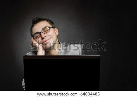 dreaming businessman with laptop on black background