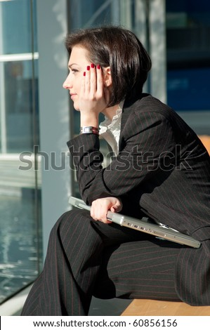 Dreaming businesswoman with a laptop - stock photo