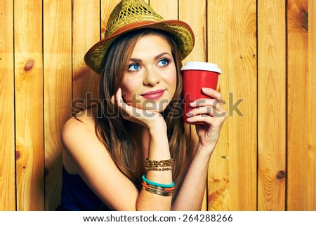 Dreaming Hipster Girl Holding Coffee Cup. Portrait on wooden background. Yellow hat. Thinking smiling model with long hair. - stock photo