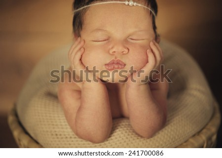Dreaming Naked Newborn Baby Lying on Hands in Basket - stock photo
