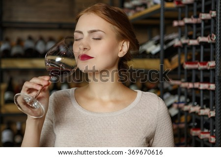 Dreaming of France. Beautiful young woman examining red wine smelling  - stock photo
