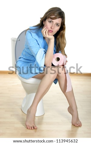 Dreaming on a toilet. Young woman sit on a toilet with toilet paper roll in her hand. - stock photo