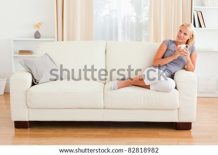 Dreaming woman holding a cup of coffee in her living room - stock photo