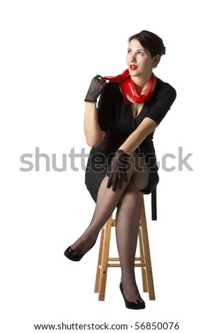 Dreaming woman on a stool, looking sideways - stock photo