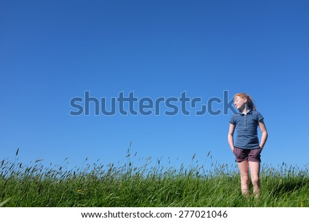 Dreaming young girl standing in meadow with blue sky