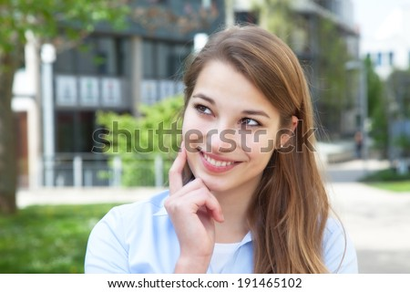 Dreaming young woman with blond hair outside - stock photo