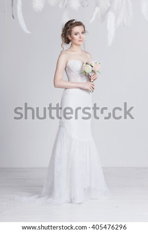 Dreamy and beautiful young bride in a luxurious lace wedding dress. She has a beautiful dark blond hair and pale skin. She is elegant and delicate. She is holding a bouquet of white and pink roses. - stock photo