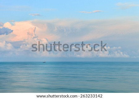 Dreamy blurred glowing sunset with clouds and a tiny boat on background - stock photo