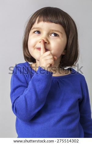 dreamy cheeky young child playing with her finger on lips for mystery - stock photo