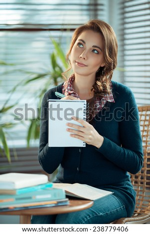 Dreamy girl writing - stock photo