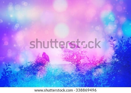 Dreamy scene with starling birds sitting on tree branches in the garden with bokeh lights - stock photo