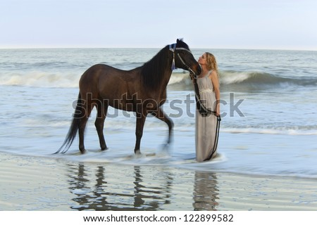 dreamy shot of woman in the ocean with her horse, time exposure with wave motion - stock photo