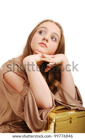 Dreamy teenage girl props the jaw her hands. She is sitting and looking sideways. Her arms are put on the golden bag in the form a trunk. - stock photo