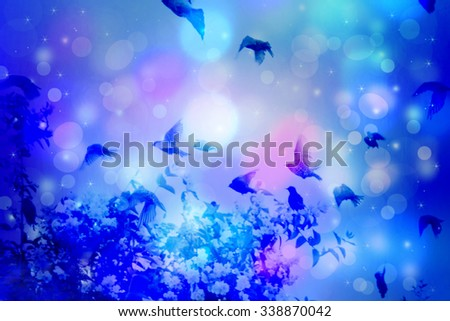 Dreamy winter scene with starlings flying in the garden at night with bokeh lights - stock photo