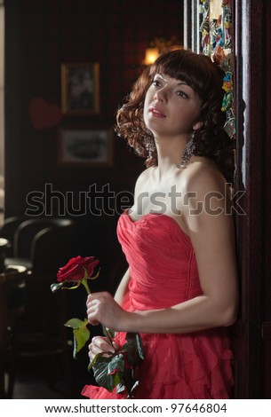 Dreamy woman in red with the rose - stock photo