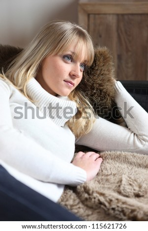 Dreamy woman lying on a sofa - stock photo