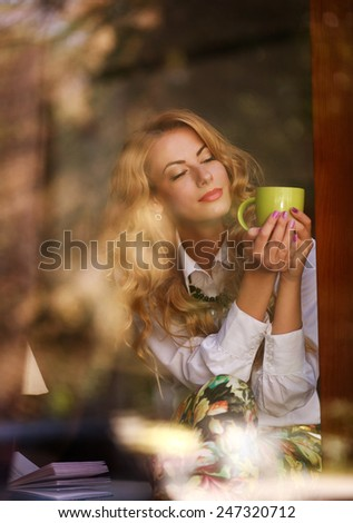Dreamy woman with a cup of coffee in cafe, enjoying the aroma of beverage, view through the window - stock photo