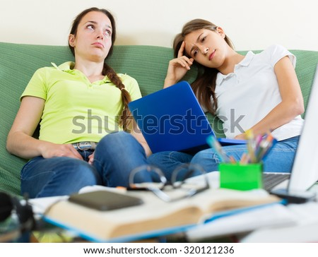 Dreary teenage student girls study in home with a books and computers