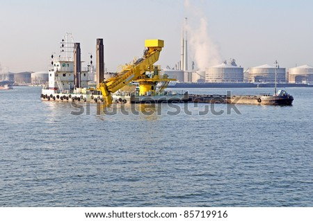 dredge ship working in the harbor of antwerp belgium with heavy industry as background - stock photo