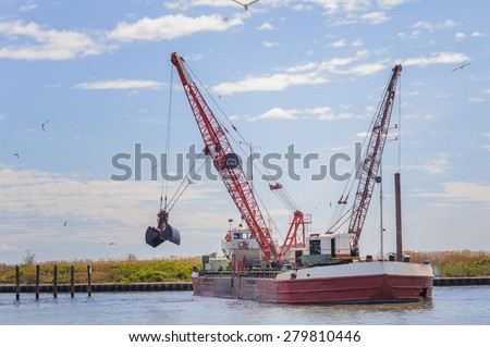 Dredger ship navy working to clean a navigation channel - stock photo