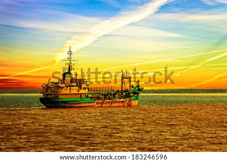 Dredger ship working in the port at sunset.  - stock photo