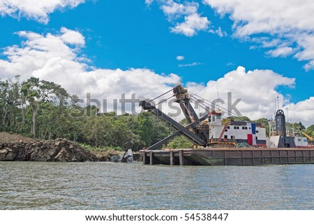 Dredging barge in canal under cloudy blue skies. - stock photo