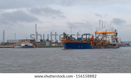 Dredging on a River near industry - stock photo