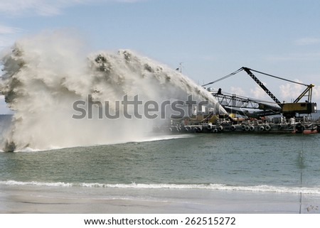 Dredging , panning sand on the beach during the construction of a new sea freight terminal in the harbor of Port - stock photo
