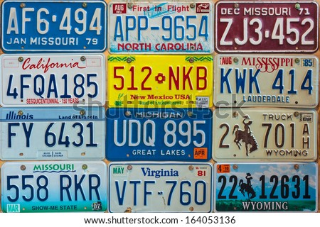 DREMPT, THE NETHERLANDS - NOVEMBER 15: Vintage car license plates on a wall on November 15, 2013 in Drempt, The Netherlands. In the U.S. each state issues its own car number plates. - stock photo