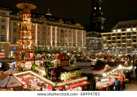 DRESDEN, GERMANY - DEC 20: Tourists enjoy Christmas market on December 20, 2010 in Dresden. One of the highlights is eight meter high Christmas pyramid with the life size hand made wooden figures. - stock photo