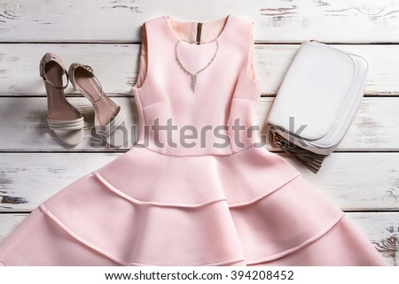 Dress and accessories on showcase. Stylish outfit on wooden background. Garment of evening collection. Warm-colored dress and jewelry. - stock photo