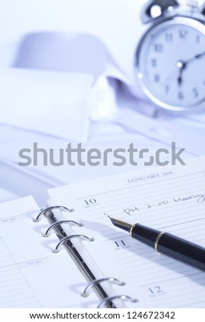 Dress shirt, alarm clock and a diary with a fountain pen